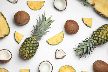 Composition with pineapple and coconut on white background, top view