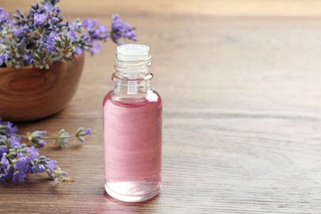 Bottle of essential oil and lavender flowers on wooden table. Space for text
