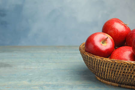Wicker bowl with ripe juicy red apples on wooden table against blue background. Space for text