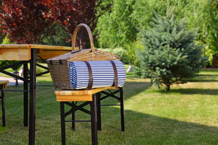 Picnic basket with blanket on wooden bench near table in green garden. Space for text Zdjęcie Seryjne