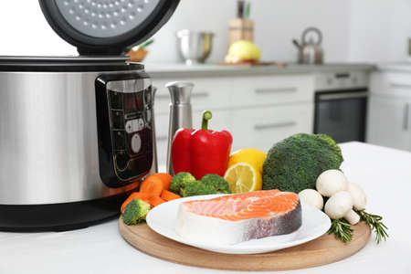 Modern multi cooker and products on kitchen table Banco de Imagens