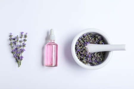 Bottle of essential oil, mortar and pestle with lavender flowers on white background, flat lay