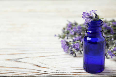 Bottle of essential oil and lavender flowers on white wooden table. Space for text