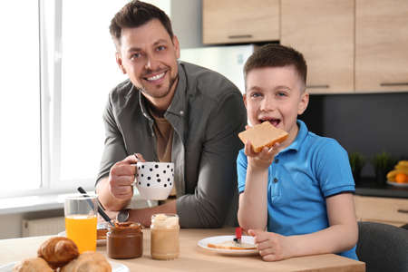 Dad and son having breakfast together in kitchen Stock Photo