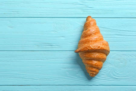 Tasty croissant and space for text on light blue wooden background, top view. French pastry