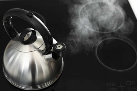Modern kettle with whistle on stove, above view. Space for text