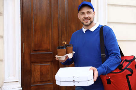 Male courier with order at entrance. Food delivery service