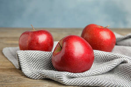 Ripe juicy red apples on wooden table against blue background