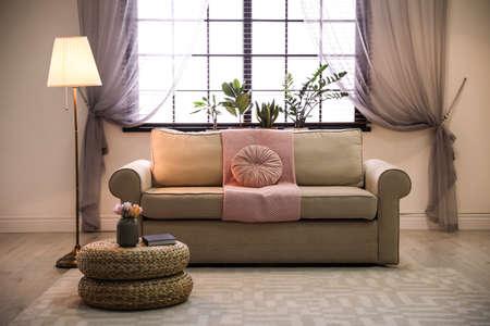 Accogliente soggiorno con mobili eleganti ed elementi decorativi. Idea per l'interior design