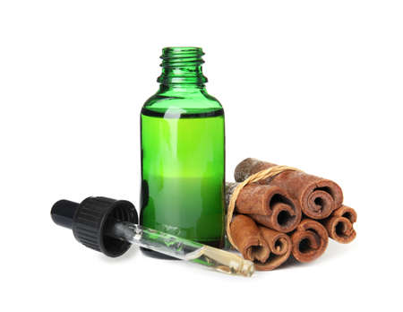 Bottle of essential oil and cinnamon sticks on white background 写真素材