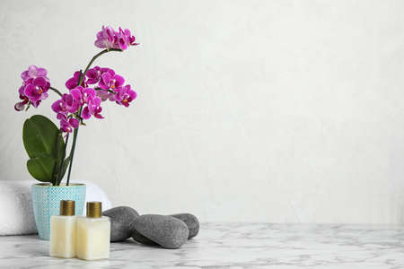 Spa accessories and blooming orchid on marble table against light background, space for text