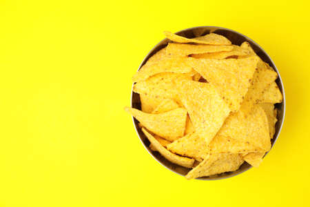 Bowl of tasty Mexican nachos chips and space for text on yellow background, top view. Space for text Banco de Imagens