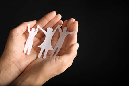 Woman holding paper silhouette of family in hands on black background, closeup. Space for text
