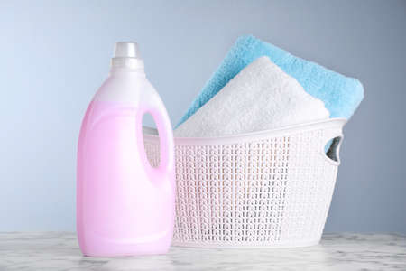 Bottle of laundry detergent and basket with towels on table Banco de Imagens
