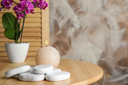 Spa stones, candle and blooming orchid indoors, space for text Stockfoto