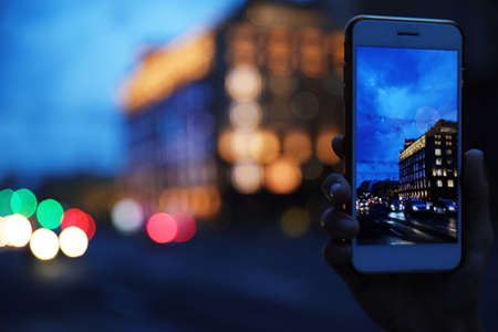 Woman taking photo of modern city in evening with smartphone, focus on hand. Bokeh effect 版權商用圖片