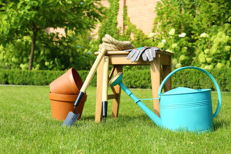 Set of gardening tools and stool on green grass Stockfoto - 128590870