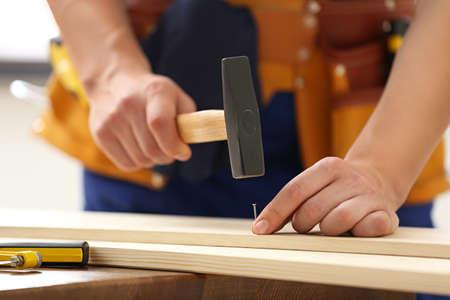 Working man hammering nail into timber indoors, closeup. Home repair
