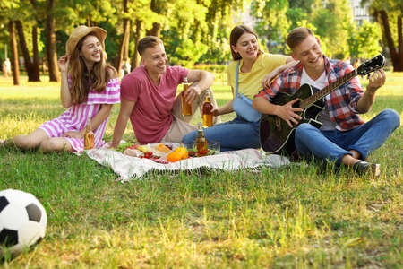 Young people enjoying picnic in park on summer day Stock Photo