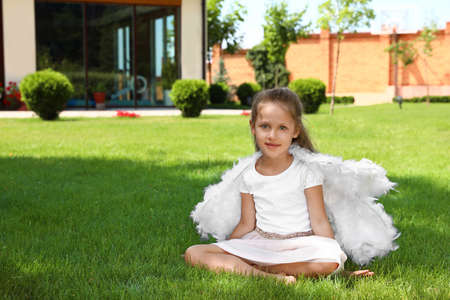 Little girl with angel wings at backyard on sunny day. Space for text