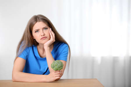 Portrait of unhappy woman with broccoli at table indoors Stock Photo