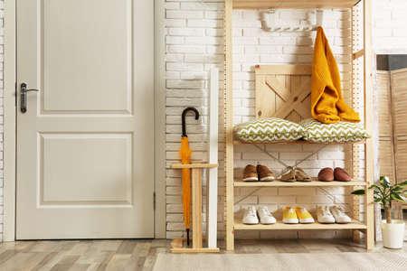 Cozy hallway interior with wooden shelving unit. Stylish design idea