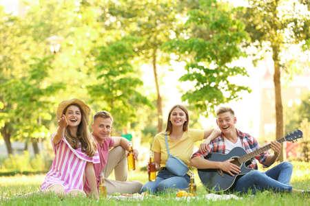 Młodzi ludzie korzystający z pikniku w parku w letni dzień