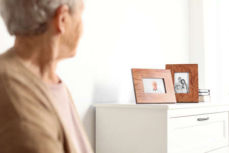Elderly woman looking at framed family portraits indoors Banco de Imagens