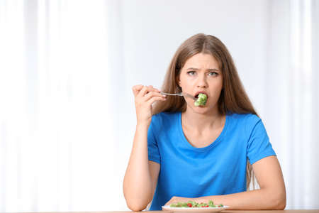 Portrait of unhappy woman eating broccoli salad at table on light background