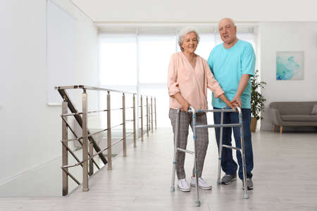 Elderly man helping his wife with walking frame indoors Imagens