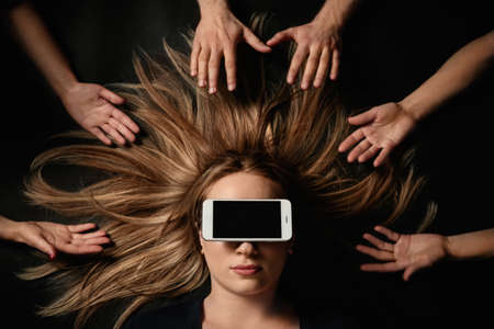 Young woman with smartphone covering her eyes surrouded by peoples hands on black background, top view. Space for text Imagens
