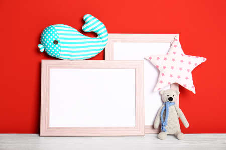 Soft toys and photo frames on table against red background, space for text. Child room interior