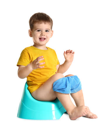 Portrait of little boy sitting on potty against white background