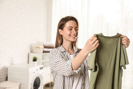 Happy young woman with clean t-shirt indoors. Laundry day Reklamní fotografie