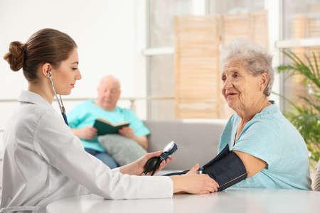 Infermiera che misura la pressione sanguigna della donna anziana all'interno. Assistere le generazioni più anziane