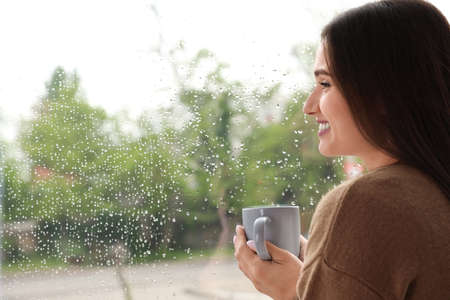 Beautiful woman with cup of coffee smiling near window indoors on rainy day Banque d'images
