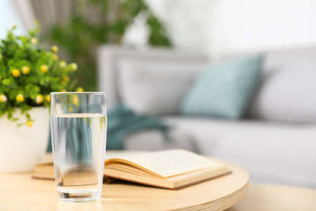 Glass of water and book on coffee table in modern living room interior. Space for text