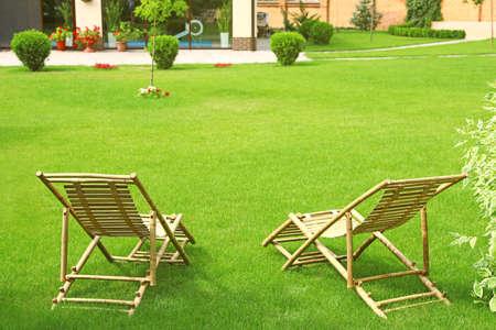 Houten ligstoelen in prachtige tuin op zonnige dag