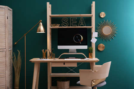 Stylish room interior with modern workplace at color wall