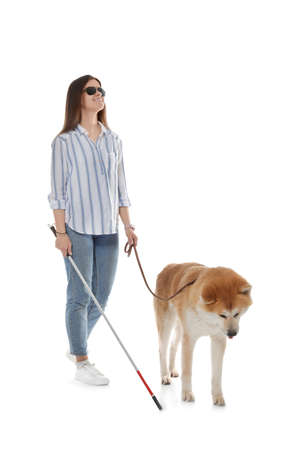 Blind woman with walking stick and dog on leash against white background Stock Photo