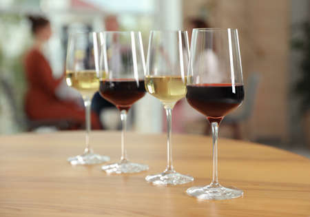 Glasses with different wines on table against blurred background