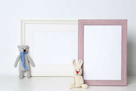 Soft toys and photo frames on table against white background, space for text. Child room interior Imagens