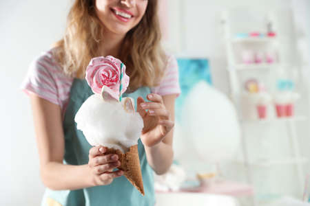 Young woman with cotton candy dessert indoors, closeup. Space for text