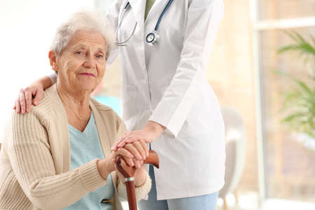 Nurse assisting elderly woman with cane indoors. Space for text Imagens