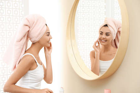 Pretty young woman with towel on head near mirror in bathroom