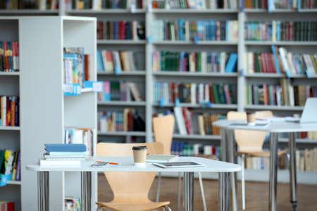 Tablet, drankje en boeken op tafel in bibliotheek Stockfoto