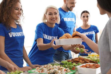 Volunteers serving food to poor people indoors