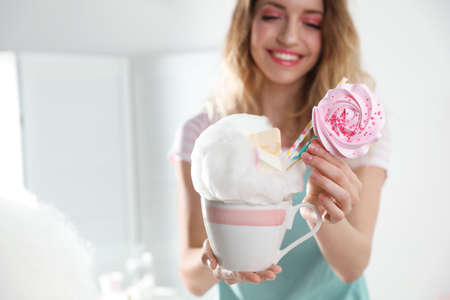 Young woman with cup of cotton candy dessert indoors, closeup. Space for text