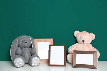Soft toys and photo frames on table against green background, space for text. Child room interior Фото со стока