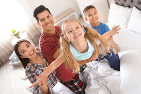Happy young family with children having fun in bedroom